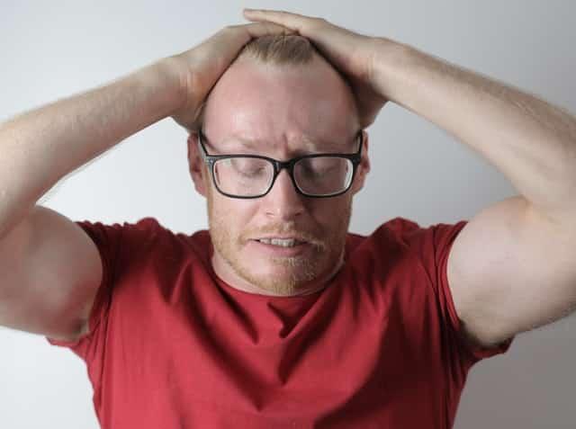 Homem com expressão de tensão com mãos na cabeça e olhos fechados