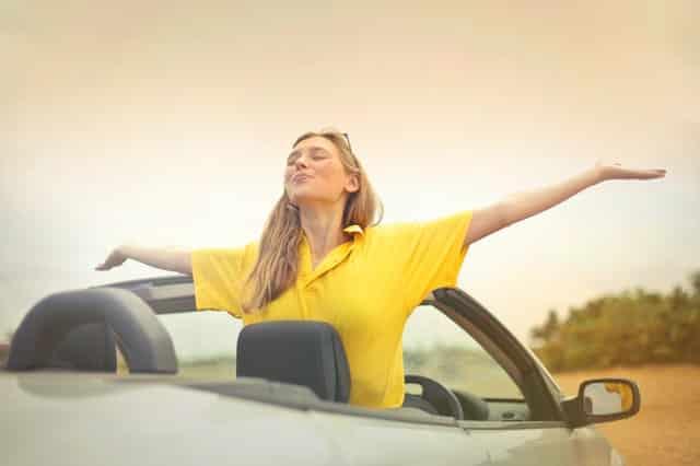 Mulher em carro conversível de braços abertos com camiseta amarela