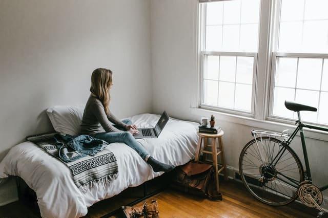 Mulher sentada na cama mexendo no notebook com quarto arrumado
