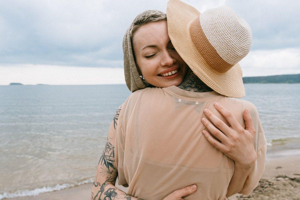 Duas mulheres brancas na praia se abraçando.