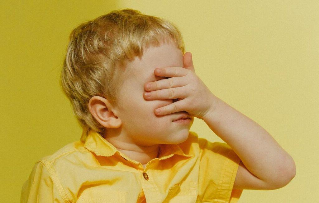 Menino branco de roupas amarelas com a mão no rosto.