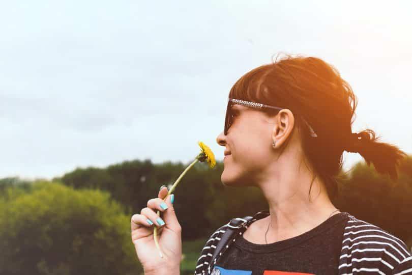 Mulher cheirando uma flor em um jardim