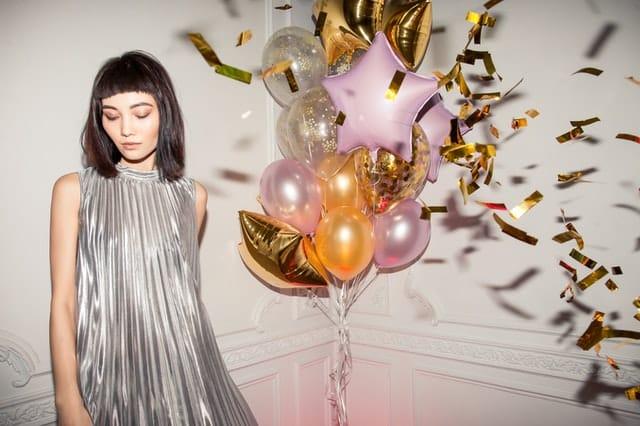 Mulher usando vestido prata com balões dourados, rosa, amarelos e transparentes ao fundo