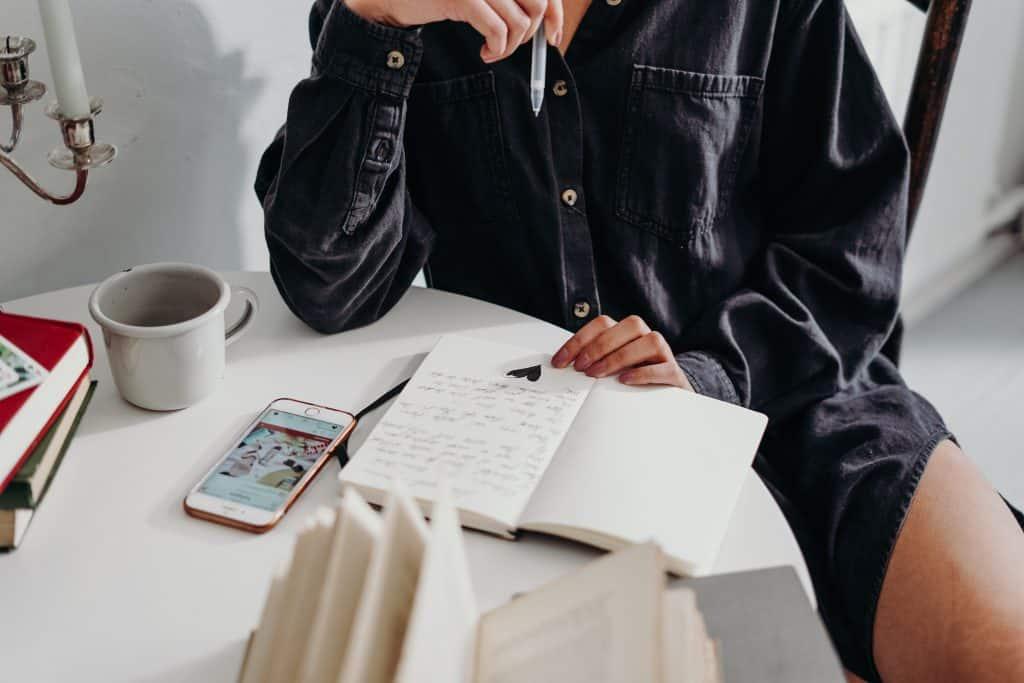 Mulher olhando para seu caderno segurando uma caneta