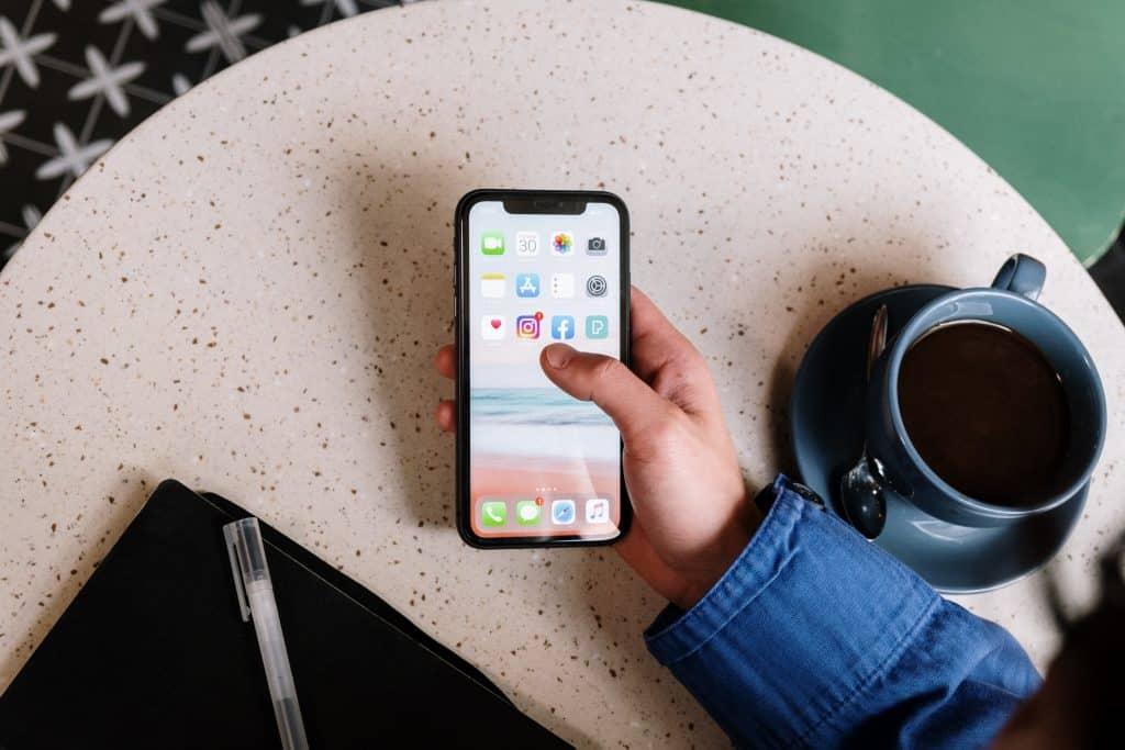 Pessoa segurando celular com aplicativos ao lado de uma xícara de café