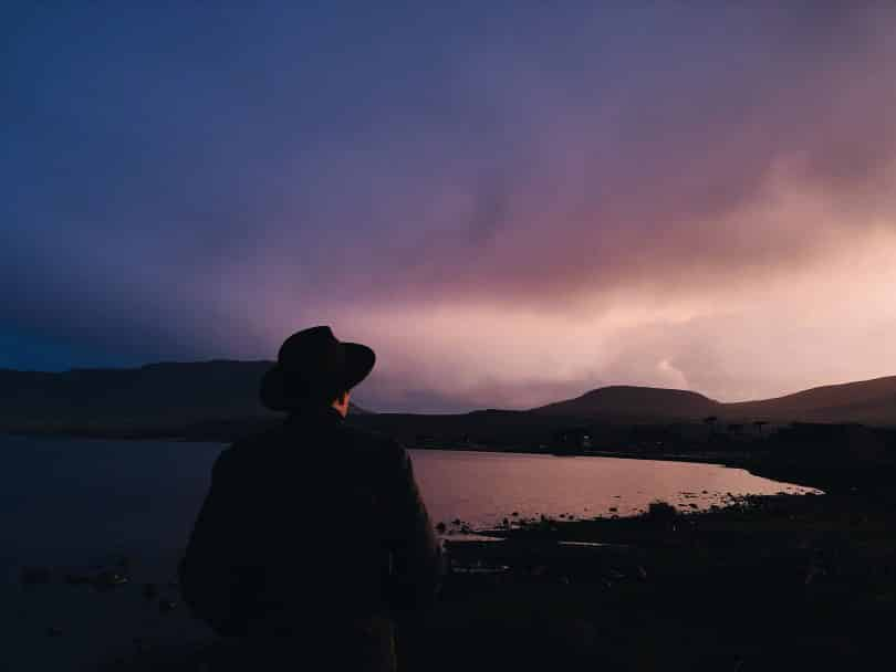 Pessoa usando chapéu ao lado de um lago ao anoitecer