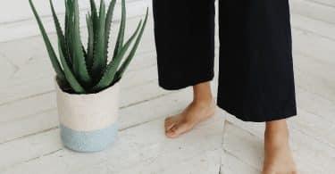 Mulher descalça com os pés no chão ao lado de um vaso