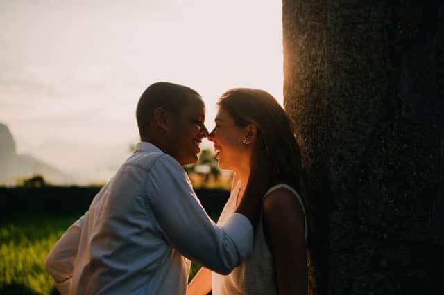 Casal sorrindo com homem com mão na nuca de mulher e sol ao fundo refletindo levemente