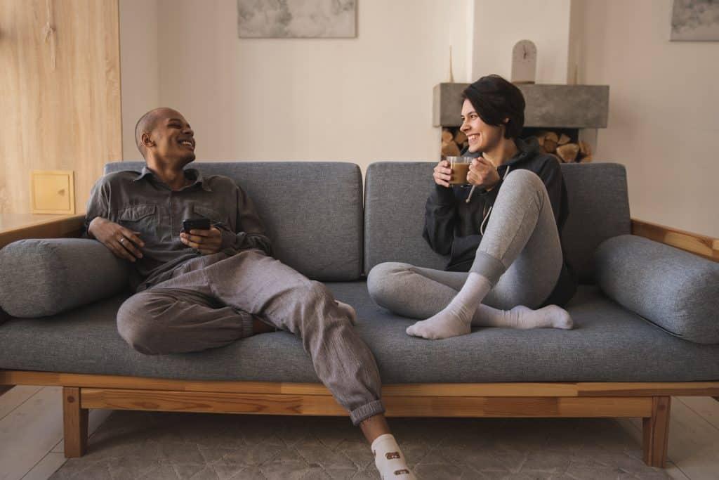 Homem e mulher sentados no sofá sorrindo