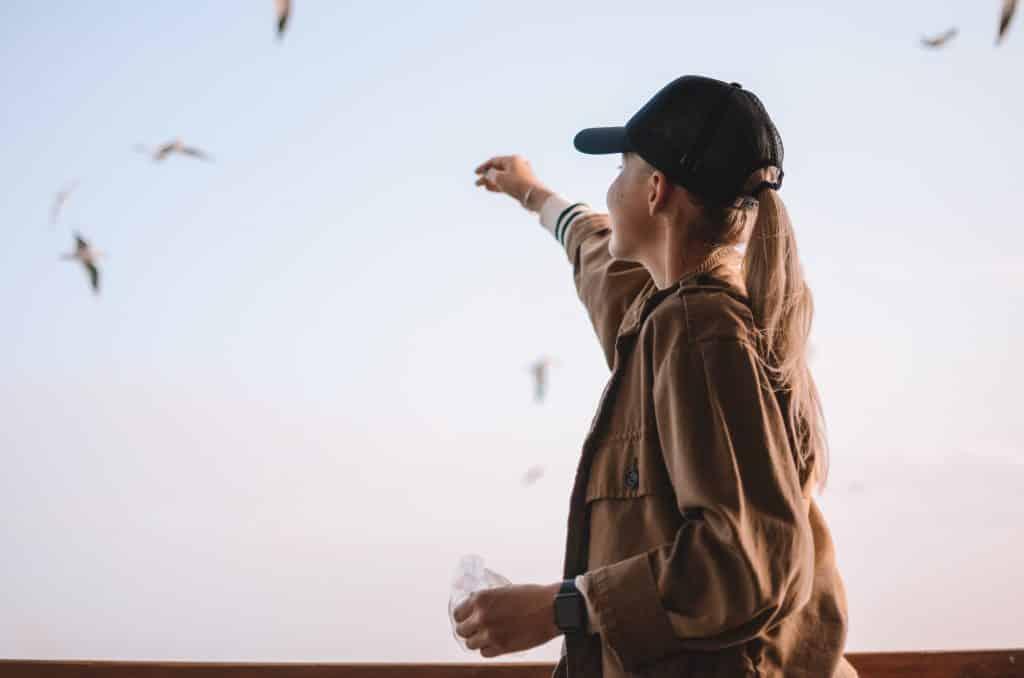 Mulher sorrindo olhando para pássaros no céu