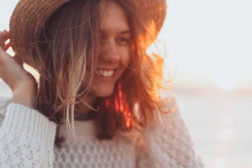 Mulher segurando chapéu e sorrindo