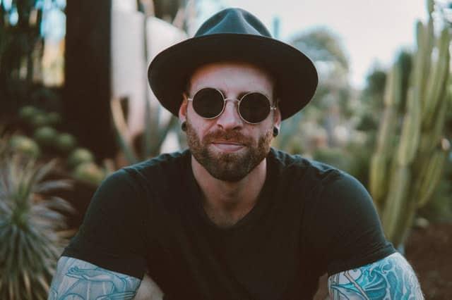 Homem visto de frente com chapéu, óculos de sol e camiseta preta