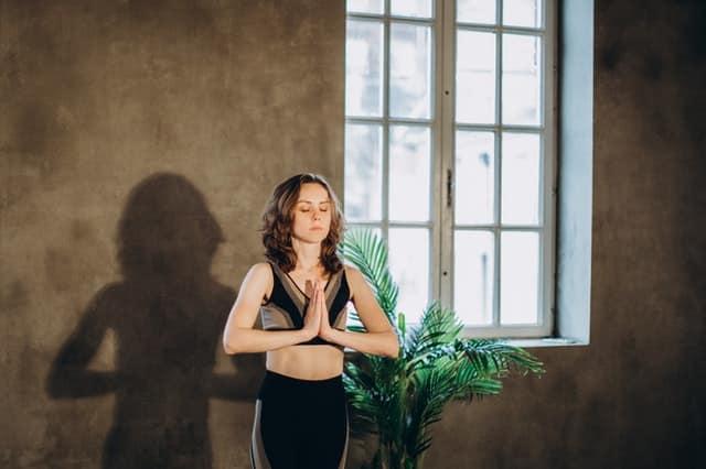 Mulher em pé meditando de olhos fechados e mãos unidas em frente ao corpo