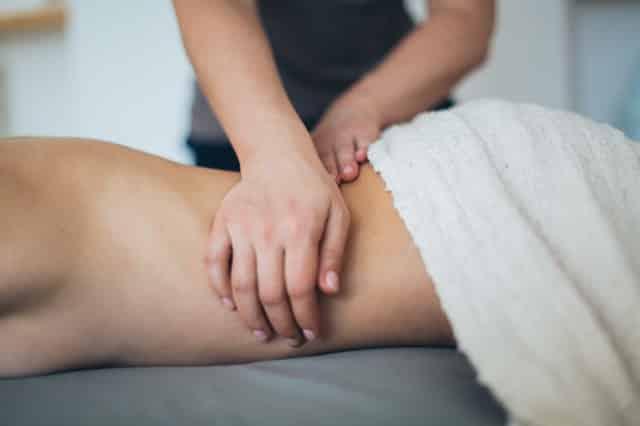Par de mãos brancas femininas realizando massagem em corpo feminino branco.