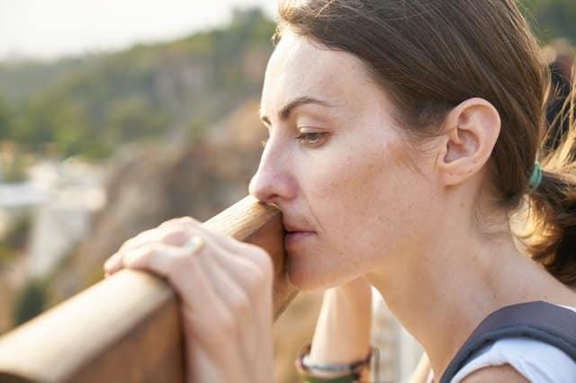 Mulher com rosto apoiado em ponte de madeira com expressão triste