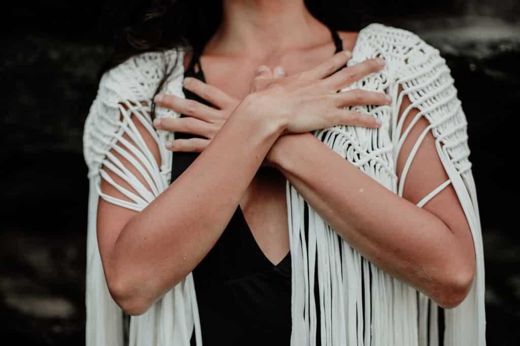 Mulher branca com braços cruzados no colo.
