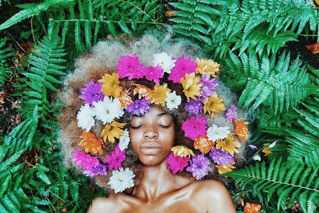 Mulher deitada com flores coloridas no cabelo de olhos fechados vista de cima
