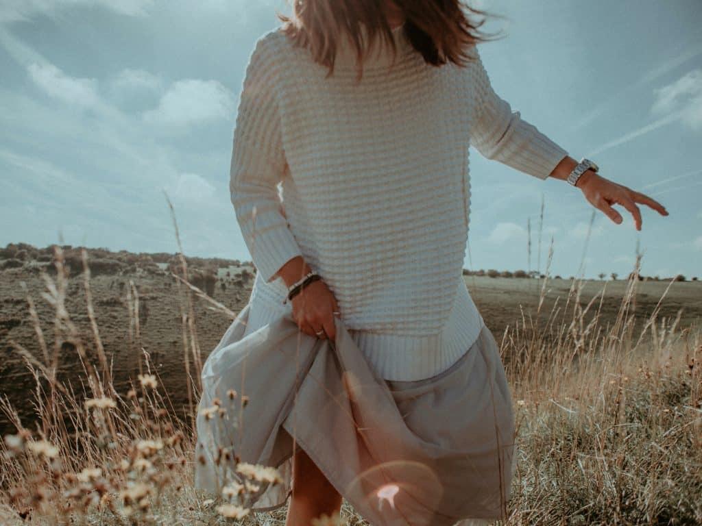Mulher andando em um campo de flores segurando a barra do vestido