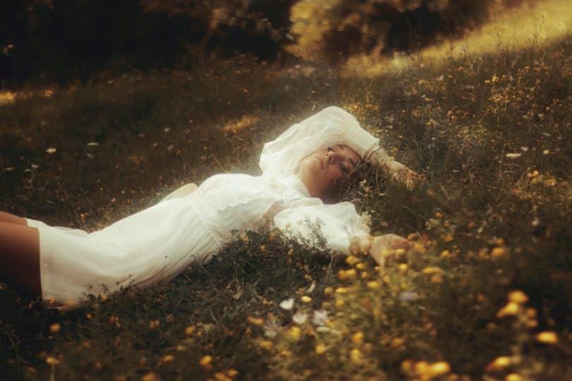 Mulher deitada em um gramado usando vestido