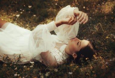 Mulher deitada em um gramado olhando para suas mãos