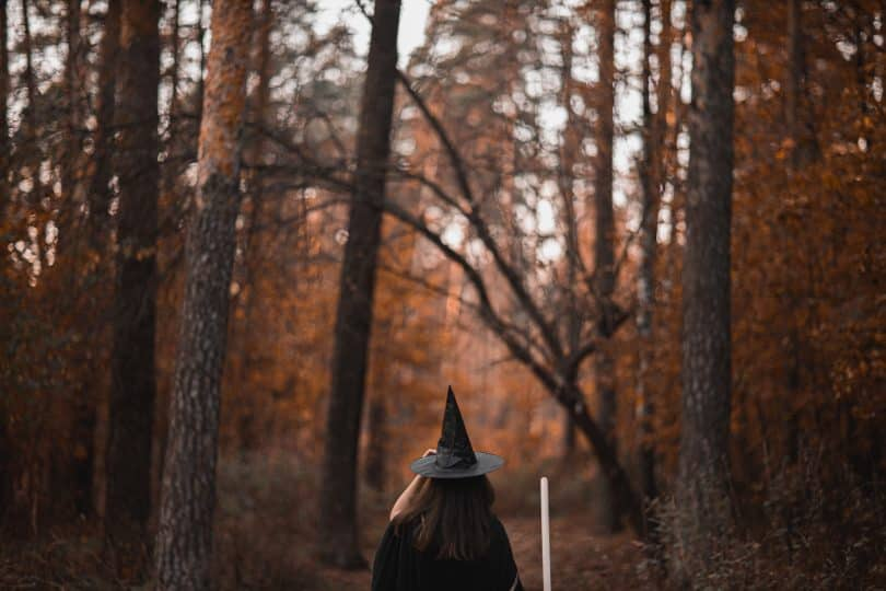 Mulher em uma floresta com roupas de bruxa