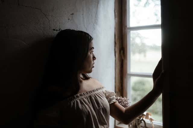 Garota olhando pela janela em quarto escuro de perfil