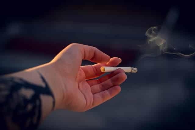 Mão segurando cigarro queimando