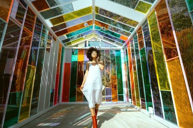Mulher de vestido branco em pé em casa com vidros coloridos