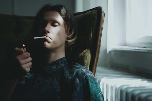 Garoto sentado em cadeira acendendo cigarro