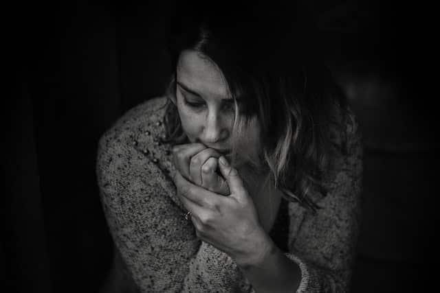 Mulher sentada roendo unha em foto preta e branca