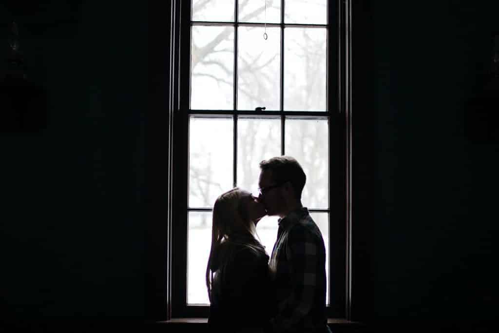 Homem e mulher se beijando em frente a uma janela.
