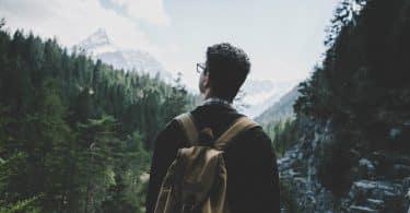 Homem de mochila nas costas olhando para árvores