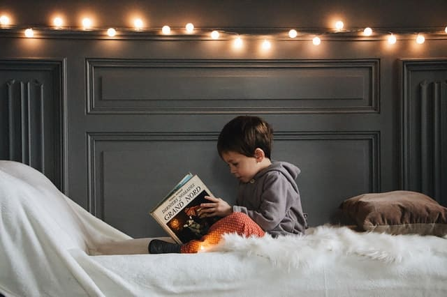 Garoto sentado em cama abrindo livro com luzes de bolas acesas