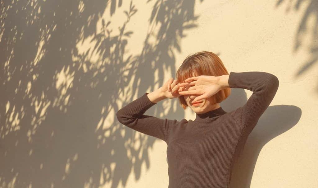 Mulher com as mãos no rosto devido ao sol
