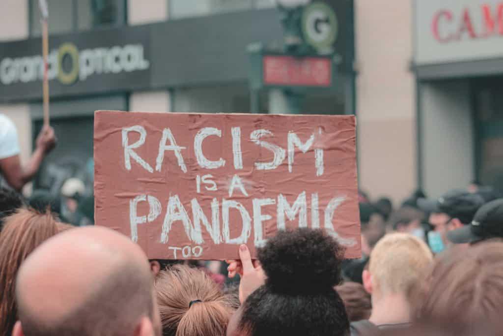 """Manisfestação na rua com uma mulher segurando um cartaz escrito """"Racismo é uma pandemia também"""""""