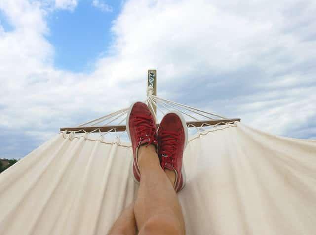 Pés com tênis em rede para cima com céu azul e nuvenso ao fundo