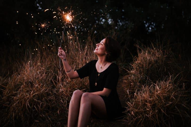 Mulher sentada em um gramado sorrindo segurando uma vela