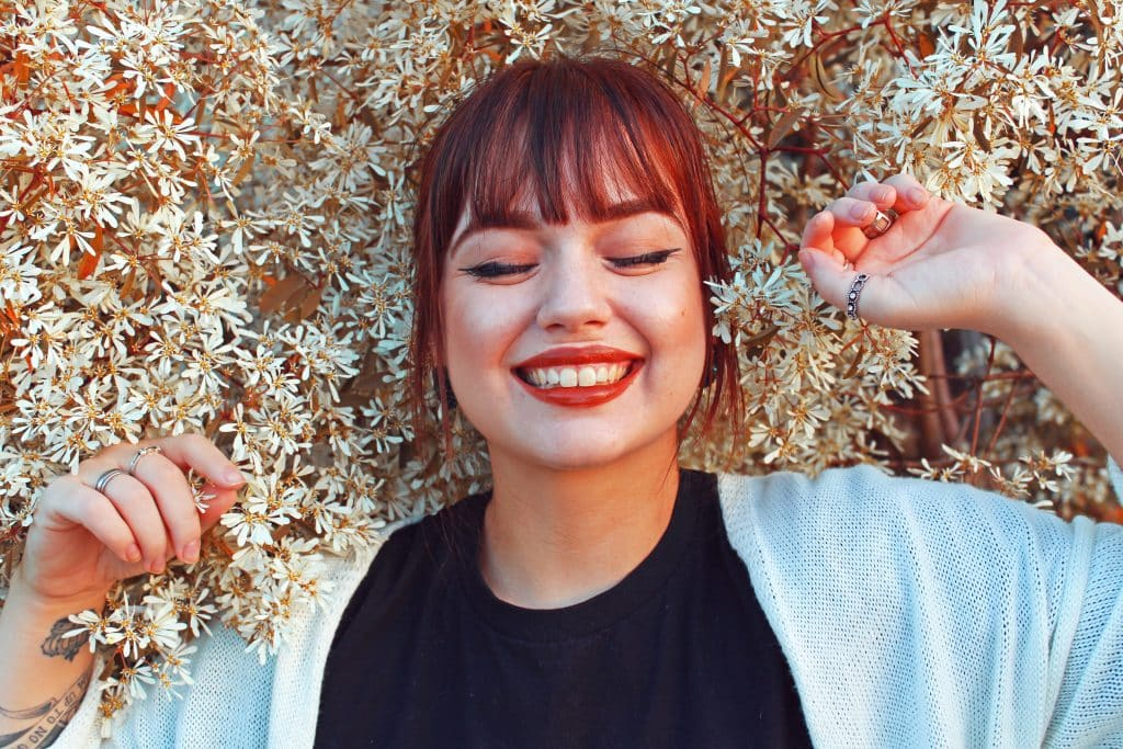 Mulher deitada em flores de olhos fechados e sorrindo