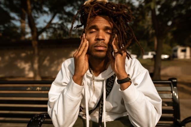Homem sentado em banco de madeira com olhos fechados e mão na cabeça