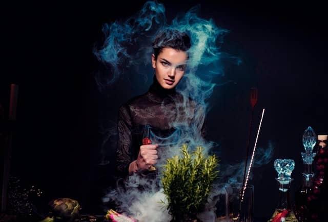 Mulher fazendo experimentos com fumaça azul em volta