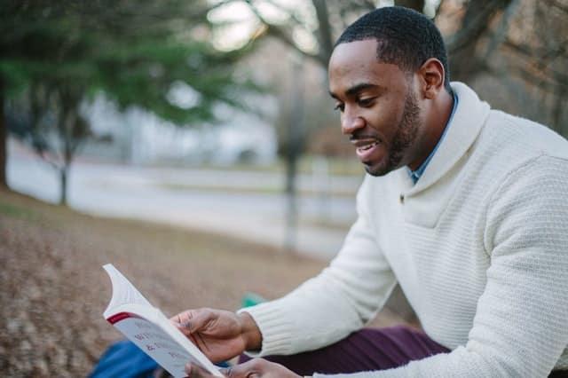 Homem sentado lendo livro