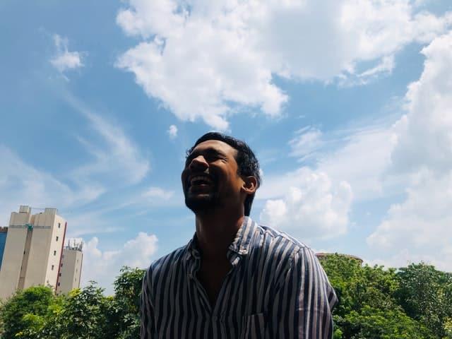Homem em pé sorrindo visto de baixo para cima com céu ao fundo sorrindo