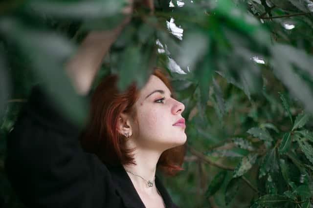 Mulher entre galhos de árvore com expressão séria de perfil
