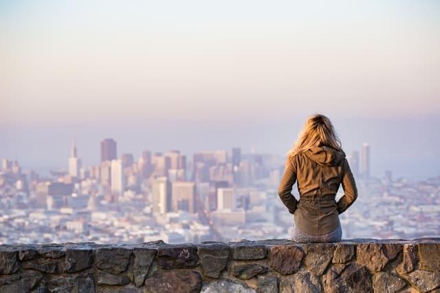 Mulher em pé apoiada em mureta de pedras olhando cidade ao fundo