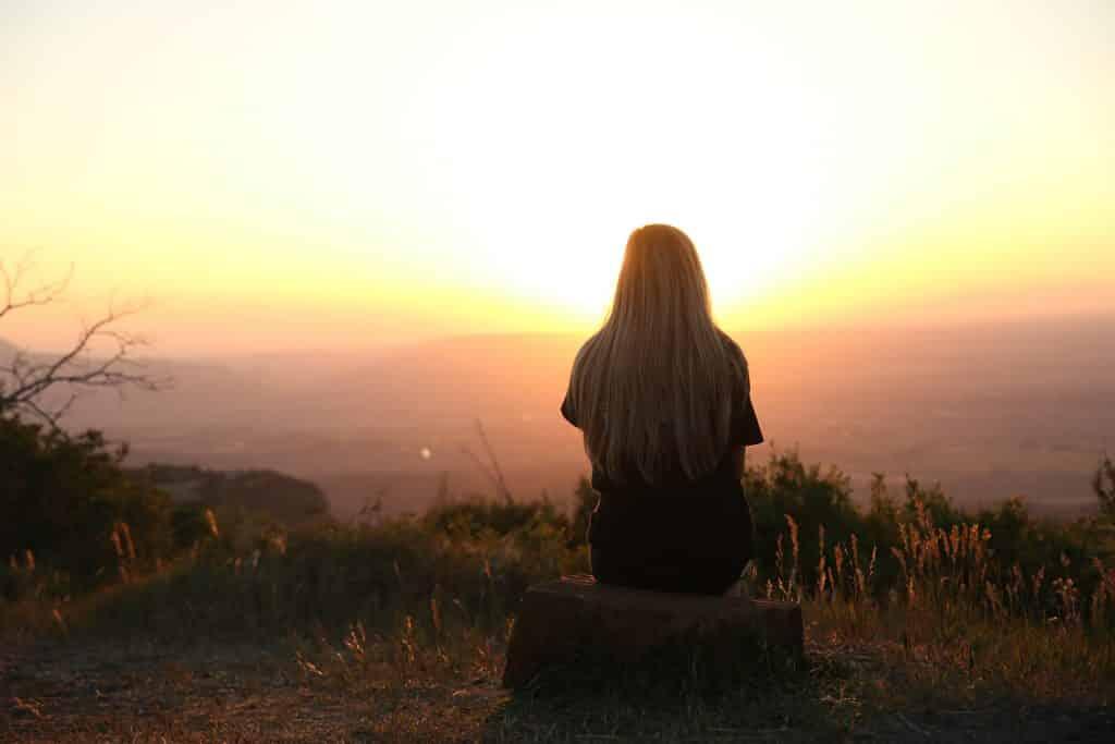 Mulher olhando para  o pôr do sol