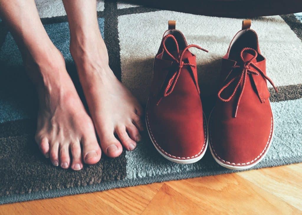 Pessoa descalça ao lado de seu sapato