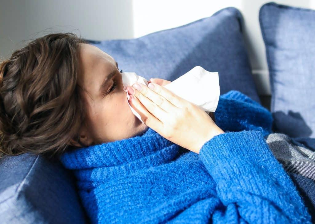 Mulher deitada limpando o nariz com papel