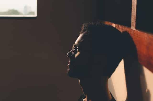 Homem na luz da janela usando óculos de perfil com expressão apática