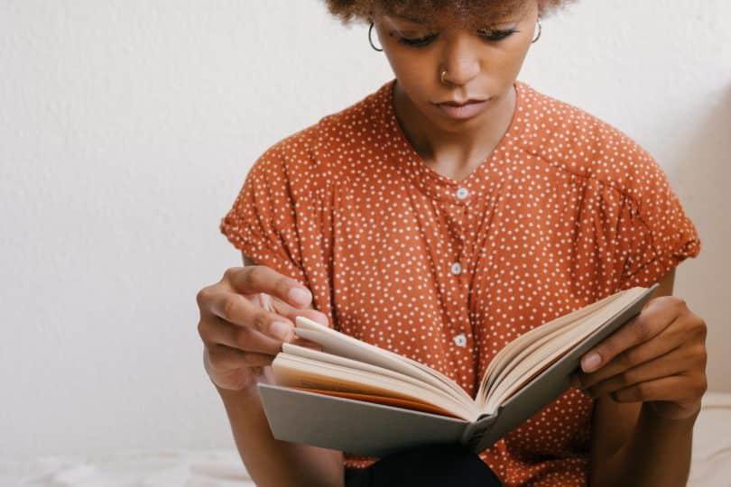 Mulher segurando um livro e lendo