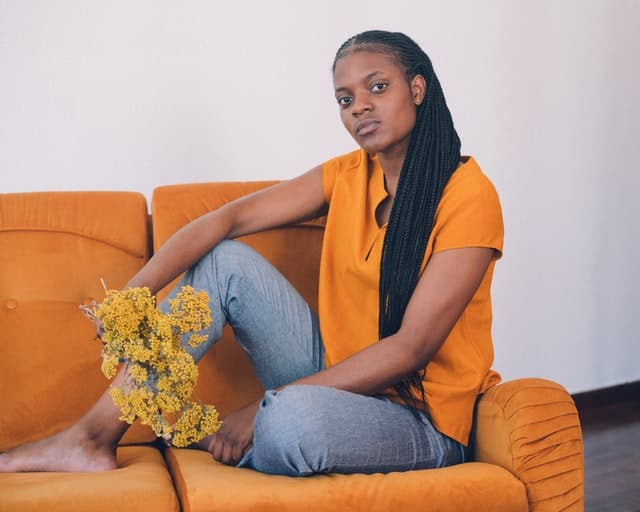 Mulher sentada em sofá com galhos de flores usando camiseta laranja